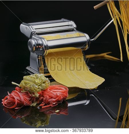 Chrome Paste Machine With Dough And Products Against Black Background