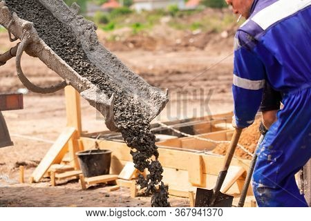 Construction Worker Laying Cement Or Concrete Into The Foundation Formwork With Automatic Pump