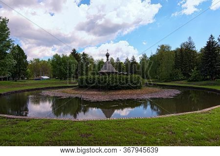 Pereyaslav, Ukraine-may 16, 2020:panoramic View Of Pond With Small Island And Wooden Arbor Against B