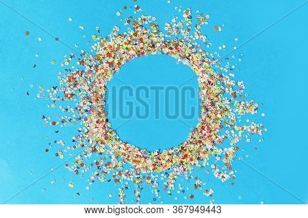 Round Frame Made Of Colored Confetti. Blue Background. Festive Confetti.
