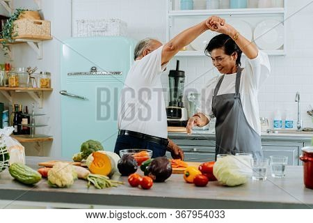 Asian Senior Couple Dancing And Smiling In Kitchen. 70s Elderly Man And Woman Cooking Together At Ho