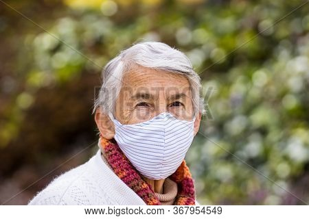 Senior Woman Wearing A Home Made Face Mask And Enjoying Some Time Outdoors During The Coronavirus Qu