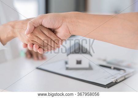Estate Agent In Suit Sitting In An Office Desk Shaking Hands With Customer After Contract Signature