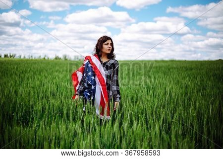Young Woman Wrapped In An American Flag On The Green Wheat Field. Patriotic Holiday Celebration. Uni
