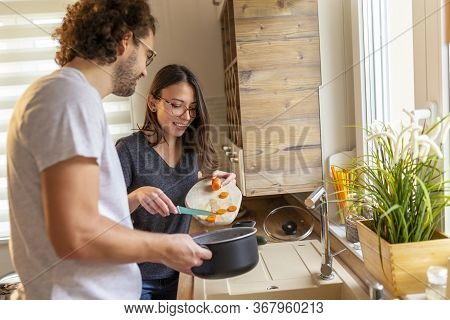 Couple In Love Having Fun In The Kitchen Preparing Food Together, Cutting Vegetables And Making Vege