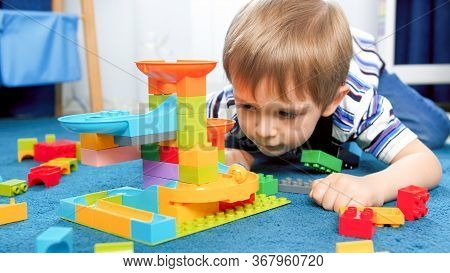 Portrait Of Little Concentrated Boy Lying On Floor And Looking On Toy Marble Run Game