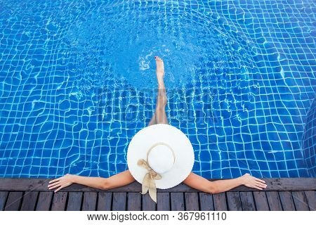 Beautiful woman sunbathing by the pool top view, summer vacation resort background. Girl sitting in swimming pool in big sunhat