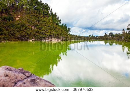 Volcanic Valley Waimangu. Crater Lake is a large hot spring and bright green water. Wai-O-Tapu Geyser Park. New Zealand, North Island. The concept of exotic, ecological and photo tourism