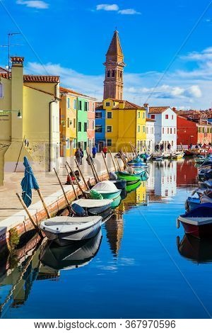 Colorful bright houses and an inclined tower are reflected in the canals of the island of Burano. Boats are parked along the banks of the canals. Venice. The concept of cultural and photo tourism