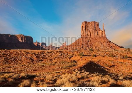 The famous cliffs Mittens in Monument Valley. The rocks - outcrops made of red sandstone. Bright multi-color sunset on the red stone valley. The concept of active, environmental and photo tourism