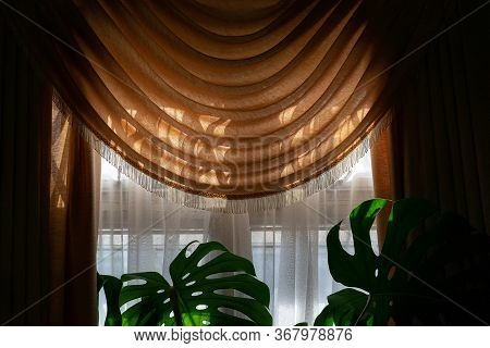 Part Of A Room Window With Translucent Thin White And A Luxurious Draped Orange Curtain At The Top A