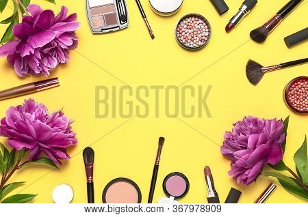 Professional Makeup Brushes, Powder, Eyeshadow, Blush, Lipstick Cream On Yellow Background Flat Lay