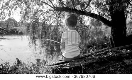 Black And White Photo Of Little Boy With Wooden Fishing Rod Catching Fish On The Lake