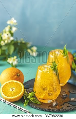 Orange Drink With Ice. Two Glass Of Orange Ice Drink With Fresh Mint On Wooden Turquoise Table Surfa