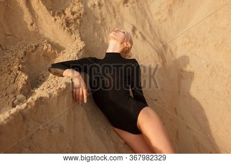 Woman In Black Bodysuit Lies On The Sand Ground. Frontal View.