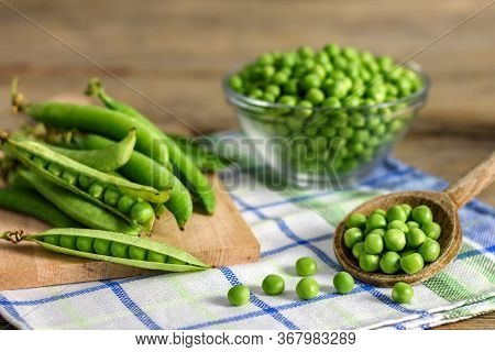 Fresh Green Peas On A Wooden Ladle And Peas In Pods On A Kitchen Cloth.