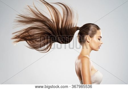 Profile portrait of a beautiful woman with a long  hair. Young  brunette model with  beautiful hair - isolated on white background. Young girl with straight hair flying in the wind.