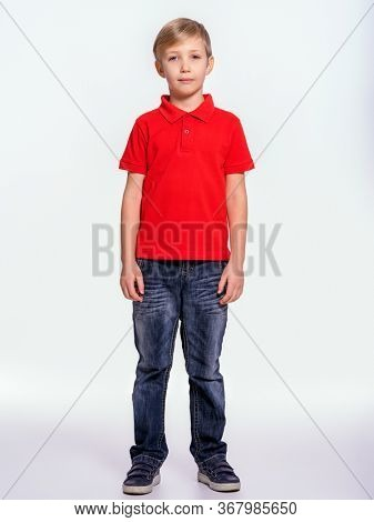 Young pretty boy posing at studio as a fashion model. Photo of a 8 years old kid. Full portrait of boy, isolated.  Portrait of white kid in a red t-shirt and jeans. Boy in a full length