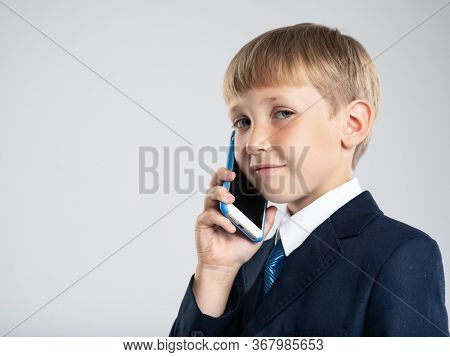 Photo of a  businessman  boy with smartphone .  Portrait of white  kid in a blue business suit holds a cell phone. 8 years old child dressed in a business formal suit with tie talking by phone