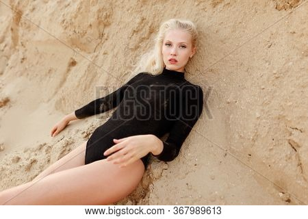 Beautiful Young Blonde Woman In Black Bodysuit Lies On The Sand Ground. Frontal View.