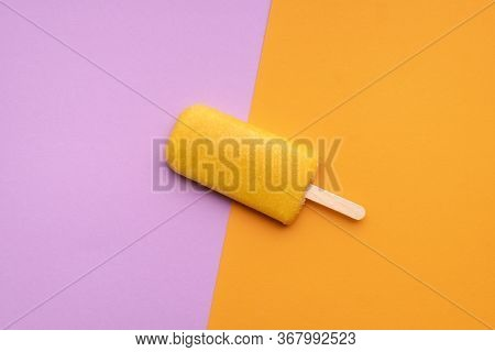 Orange Flavored Ice Cream Popsicle On A Seamless Colorful Background. Flat Lay Of One Fruity Popsicl