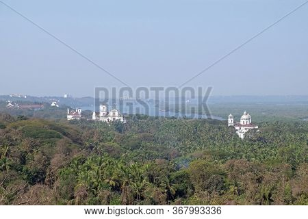 OLD GOA, INDIA - FEBRUARY 18, 2020: Old Goa along Mandovi River with Se Cathedral in front of Church of St Francis of Assisi, left, and Church of St Cajetan, right, Goa, India