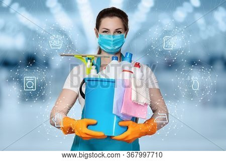 The Concepts Of Cleaning And Disinfection Services.a Cleaning Lady In A Mask Stands On A Blurry Back