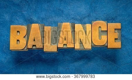 balance word in vintage wood type against blue handmade bark paper, harmony,  stability,  equilibrium and finance concept
