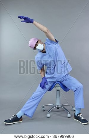 Caucasian dentist in uniform, mask and eyeglasses , stretching arms and body  in studio - healthy lifestyle at work