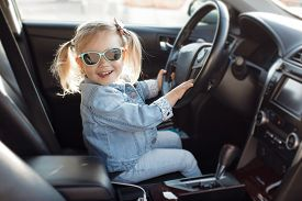 Cute Little Girl Behind Wheel Of Car.baby Girl Sitting On The Driver\'s Seat In A Family Car.child D