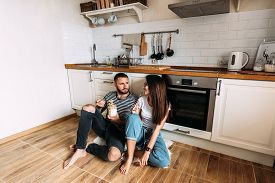Young Man And Woman Sitting On Floor In Kitchen And Talking. Loving Young Couple Spending Time Toget