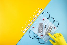 Protective Medical Masks, Pills And Syringe On Blue And Yellow Background. . Protection Against Viru