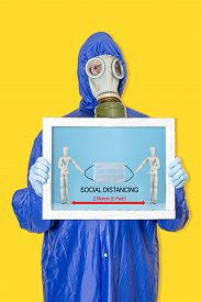 Social Distancing. A Man In A Gas Mask With A Banner On A Yellow Background. Coronavirus Quarantine