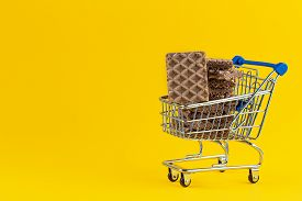 Crunchy And Tasty Waffle In Small Shopping Cart On Bright Yellow Paper Background. Toy Shopping Cart
