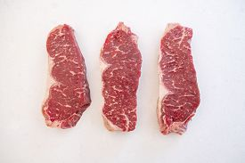 Three Raw Beef Strip Loin Steak Side By Side On A White Quartz Kitchen Countertop