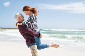 Mature couple hugging on the beach. Senior active man lifting beautiful mid woman on the beach with sea in the background and copy space. Happy retired couple hugging at seaside, looking at each other