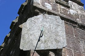 Stone Sundial On A Wall Of A Church Tower