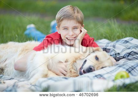 Portrait of cute lad and his fluffy pet lying on plaid poster