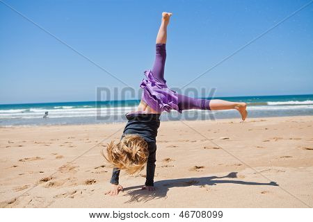 Young Girl Doing Cartwheel At Beach