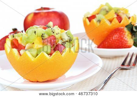 Fruit salad in hollowed-out orange isolated on white