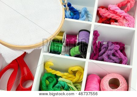 Material for embroidery in white wooden box closeup