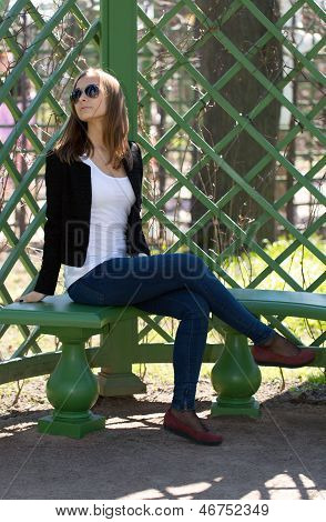 Portrait Of The Beautiful Girl Sits On A Bench In Green Park