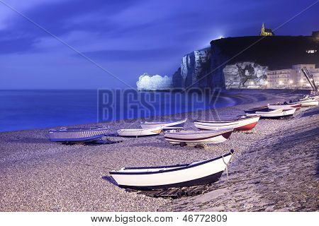 Etretat Village, Bay Beach And Boats On Foggy Night. Normandy, France.