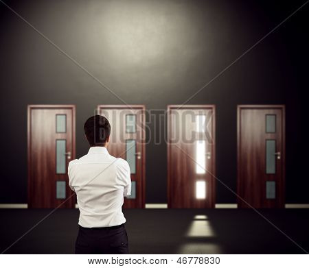 businessman looking at four doors and pondering over decision. focus on man
