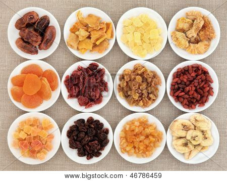 Dried fruit assortment in white porcelain bowls over hessian background.