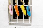 Four brightly colored traditional spanish shoes hanging outside a window poster