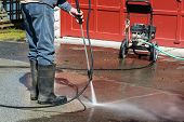 A man wearing rubber boots is pressure washing a drive way.  Lower half of man visible. poster
