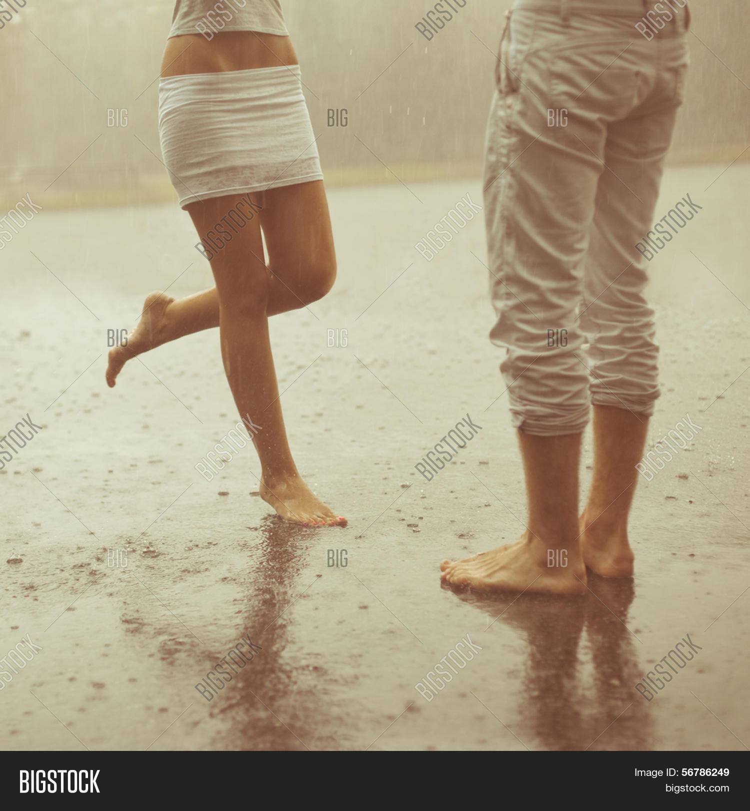 A loving young couple hugging and kissing under a rain two lovers man and