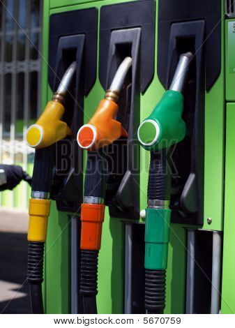 Colored fuel pumps at the petrol station poster