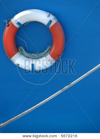 Lifebuoy and rope on blue